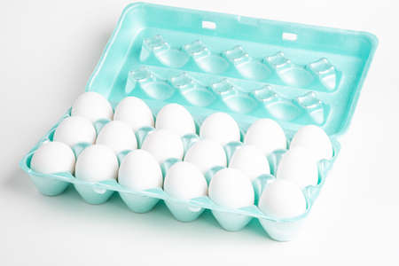 A close-up shot of a bright green polystyrene crate full of white eggs set on a white background.