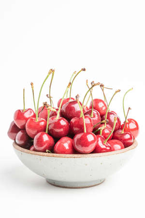 A bunch of fresh red cherries arranged and fitted in small round stoneware bowl set on plain white background.