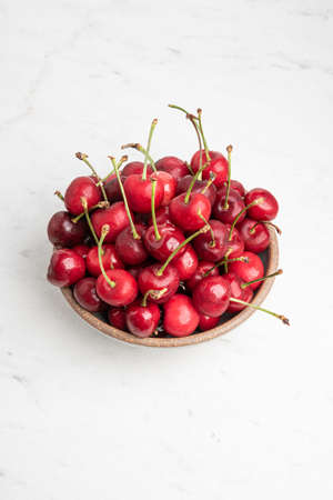 A bunch of fresh red cherries arranged and fitted in small round stoneware bowl set on plain white background. Stock Photo