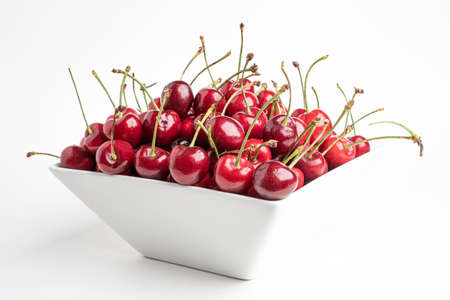 A bunch of fresh red cherries arranged and fitted in a square porcelain bowl set on plain white background.