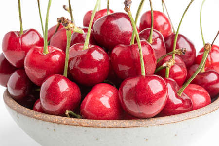 A macro shot of fresh red cherries with selective focus arranged in a bowl and set on plain white background.