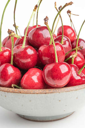A macro shot of fresh red cherries with selective focus arranged in a bowl and set on plain white background. Stock Photo