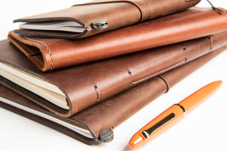 A stack of leather-bound travel writing journals with an orange fountain pen set on plain white background,