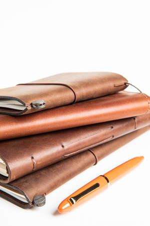 Una pila de diarios de escritura de viaje encuadernados en cuero con una pluma estilográfica naranja sobre fondo blanco liso,