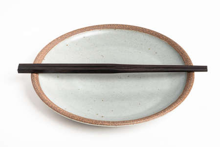 A pair of oriental black wooden chopsticks rests on a textured stoneware plate and set on plain white background.