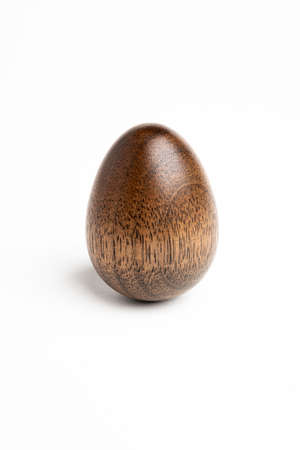 A simple sculptural piece depicting the shape of a standing egg made out of hardwood with distinctive polished texture.