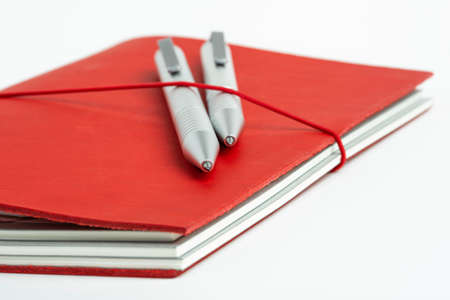 A journal with red leather cover and elastic band securing two metallic ballpoint pens.