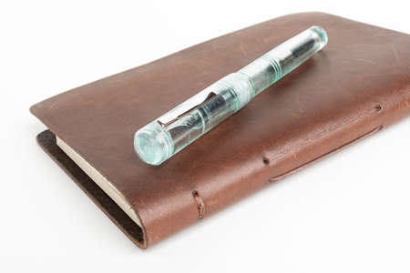 A simple but artful combination of classic leather bound journal and green glass fountain pen set on a plain white background.