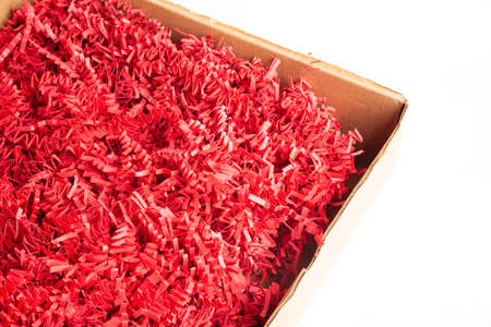 A brown cardboard package box filled with cut and crimped red paper strips set on a plain white background. Banco de Imagens