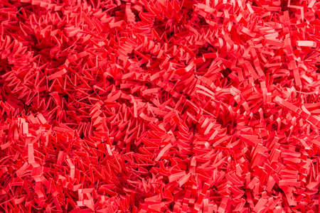 A close-up shot of a bed of cut and crimped red paper package filling strips.