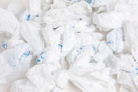 A close-up of a spread of white crumpled grocery labeled plastic bags.