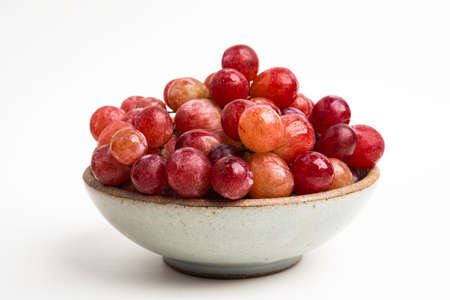 A bunch of fresh red grapes bunched on a small ceramic bowl set on a plain white background.