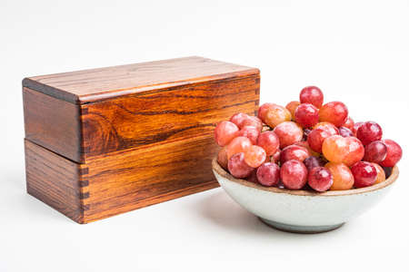 A bowl of fresh grapes with traditional 2-layer Japanese wooden bento box set on plain white background.
