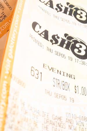 Vidalia, Georgia / USA - September 9, 2019: A close-up studio shot of the Georgia Cash 3 lottery printout ticket.