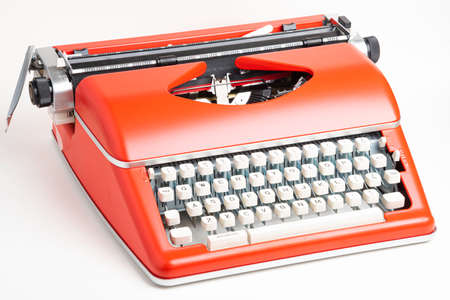 A studio shot of a retro-style portable manual typewriter with ivory-color plastic keyboard and red-orange metal casing.