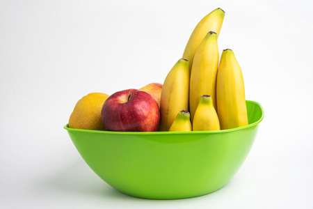 A bright green plastic bowl with artfully arranged fresh and ripe fruits such as apples, bananas, oranges, and others set on a plain white background.