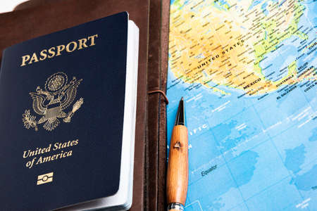 The foil-stamped dark blue front cover of an American passport with leather-covered travel notebooks and writing pen set on a world map background.