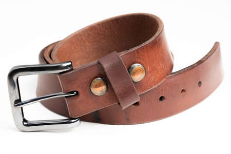 A formal studio product shot of a men's used brown leather belt with patina set on plain white background. Stock Photo