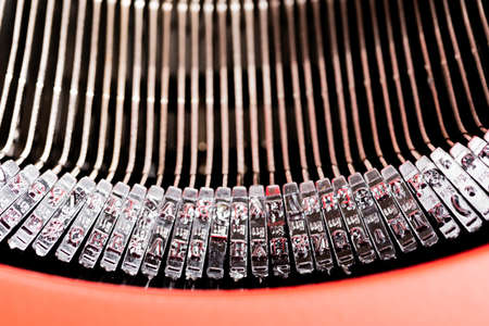 A close-up or macro shot of the type bars of a retro style manual typewriter encased in a hinged red top cover.