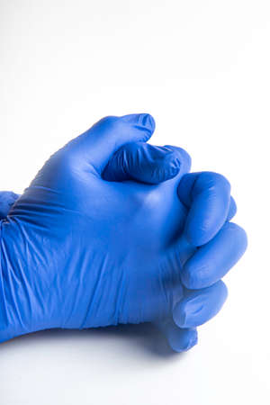 Hands wearing blue latex disposable gloves set on plain white background.