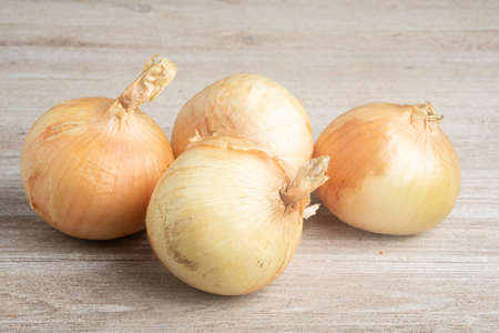 A bunch of four freshly harvested sweet white onions artfully arranged on a white painted rustic wood panel board.
