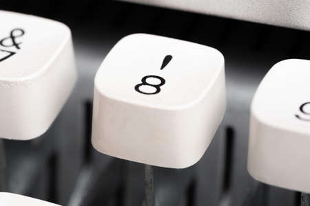 An extreme close-up or macro shot of a plastic keyboard key from a manual typewriter with shallow depth of field and selective focus.