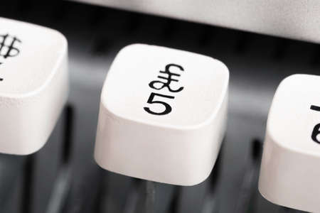 An extreme close-up or macro shot of a plastic keyboard key from a manual typewriter with shallow depth of field and selective focus. Фото со стока