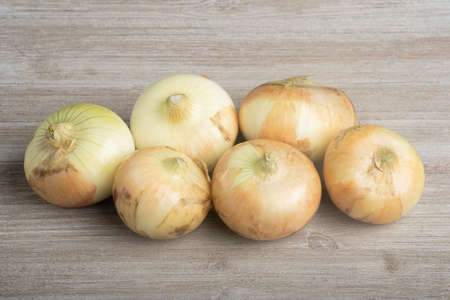A bunch of authentic southern sweet white onions artfully arranged on a white painted rustic wood panel board.