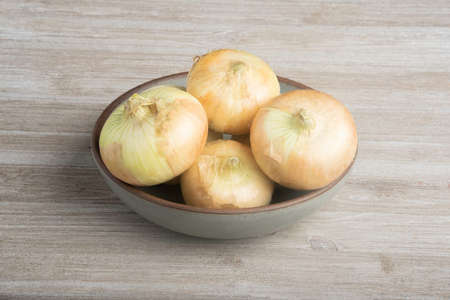 A bunch of authentic southern sweet white onions artfully arranged on a ceramic bowl placed on a white painted rustic wood panel board. Banco de Imagens