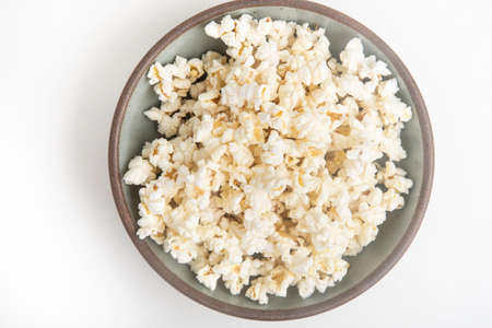 Popcorn in a ceramic bowl set on a plain white background.