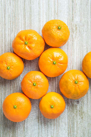 A group of fresh oranges artfully arranged on a white-painted textured wood panel board.
