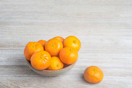 A bunch of fresh oranges in a ceramic bowl set on a white-painted textured wood panel board.