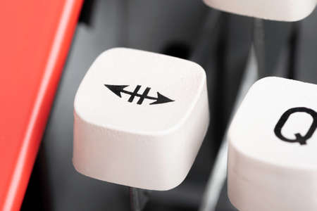 An extreme close-up or macro shot of a plastic keyboard key cap from a manual typewriter with shallow depth of field and selective focus.