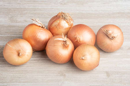 A bunch of fresh, authentic sweet southern-grown onions artfully arranged on a white painted rustic wood panel board. Banco de Imagens