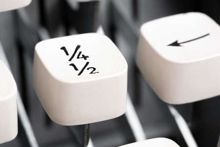 An extreme close-up or macro shot of a white plastic keyboard key cap from a manual typewriter with shallow depth of field and selective focus.