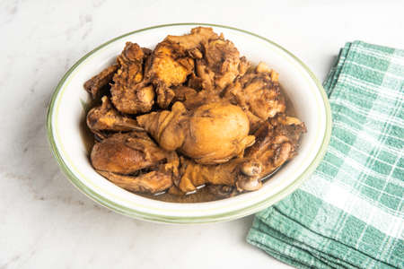 A serving of Filipino-style chicken adobo dish in a bowl with green napkin set on a marble tabletop.