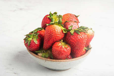 A ceramic bowl of fresh and sweet red strawberries set on a marble countertop with green napkin.