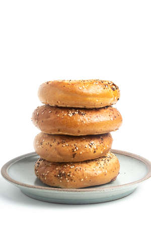 """A single tall stack of four """"everything"""" bagels on a ceramic plate set on a plain white background."""