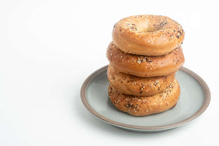 "A single tall stack of four ""everything"" bagels on a ceramic plate set on a plain white background."