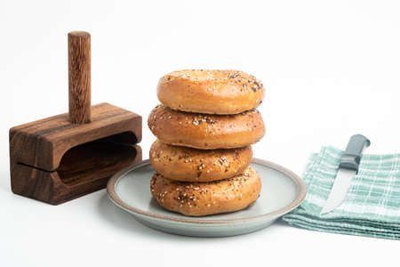 A single tall stack of four freshly baked bagels on a ceramic plate with a cutting wood stand and knife set on a plain white background.