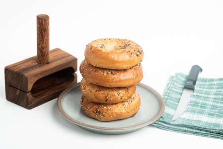 A single tall stack of four freshly baked bagels on a ceramic plate with a cutting wood stand and knife set on a plain white background. Imagens