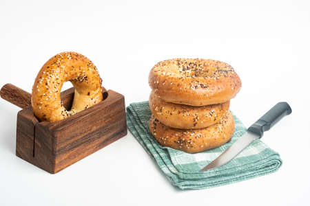 A single tall stack of three freshly baked bagels on a napkin with one bagel on a cutting wood stand and knife set on a plain white background.