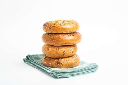 A single tall stack of four freshly baked bagels on a green napkin set on a plain white background.