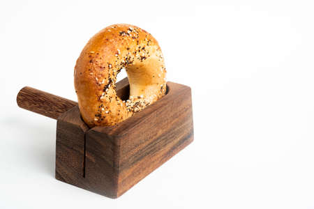 A single freshly baked bagel propped on a wood slicing stand set on a plain white background.