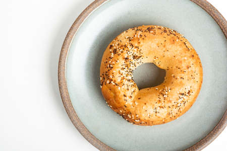 A single freshly baked bagel on a ceramic plate set on a plain white background.