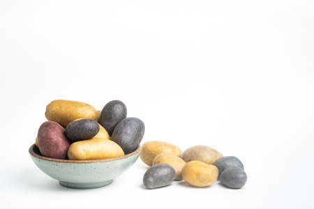 An assorted color raw and fresh potatoes artfully arranged on bowl and table set on plain white background. Stock Photo