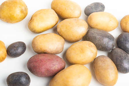 An assorted color raw and fresh potatoes artfully arranged and set on flat white surface table background. Stock Photo