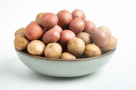 Raw and fresh baby potatoes artfully arranged in a bowl and set on white background. Stock Photo