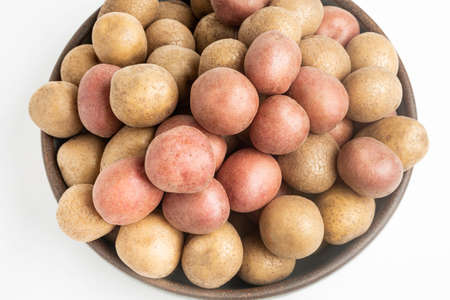 Top view of raw and fresh baby potatoes artfully arranged in a bowl and set on white background.
