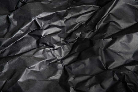 A textured and shadowy terrain of crumpled black paper as background image.